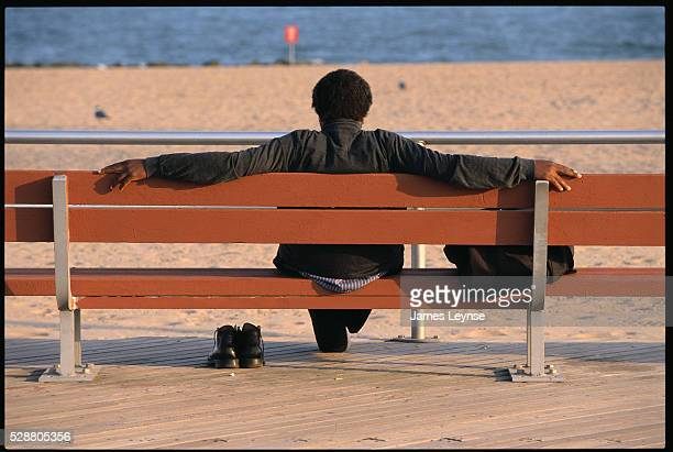 A man rests on a bench and gazes out at the water at Coney Island in Brooklyn New York