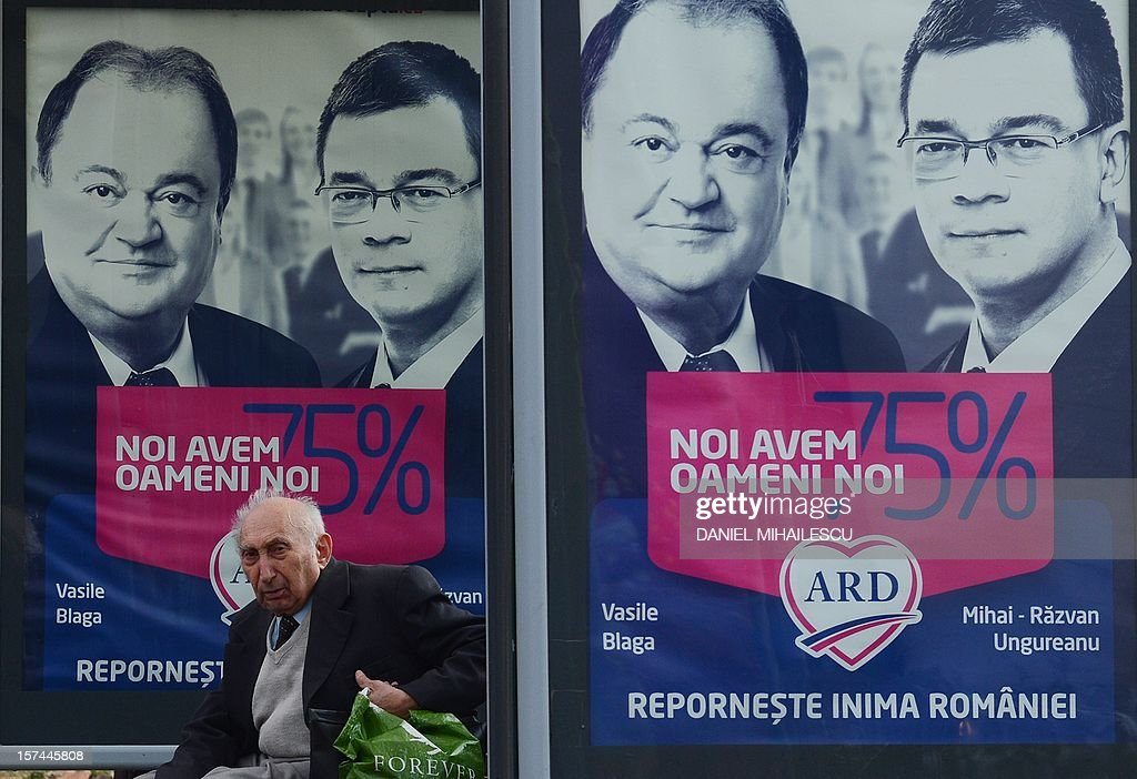 A man rests on a bench at a bus station by electoral posters of Fair Romania Alliance (ARD) opposition coallition reading in Romanian 'Restart the heart of Romania, we have new people' featuring former Prime Minister Mihai Razvan Ungureanu and former Interior Minister Vasile Blaga, in Bucharest December 3, 2012. Rulling coalition Social Liberal Union (USL) and opposition coalition ARD are the main competitors for the votes of Romanians who will go to polls on December 9, 2012 to vote for the new parliament. Romania, still recovering from a painful austerity drive, will have to walk a tightrope between cutting spending and spurring growth no matter who wins polls on December 9, analysts warn. AFP PHOTO / DANIEL MIHAILESCU. AFP PHOTO DANIEL MIHAILESCU