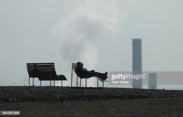 A man rests on a bench on a hill that is actually a slag heap from a former nearby coal mine as the chimney of a nearby power station stands behind...