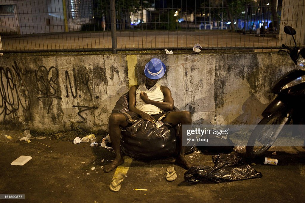 A man rests on a plastic bag outside the Sambadrome during Carnival celebrations in Rio de Janeiro, Brazil, on Monday, Feb. 11, 2013. The festivities, which are expected to attract almost 900,000 visitors, precede the start of Lent, which begins with Ash Wednesday on Feb. 13. Photographer: Dado Galdieri/Bloomberg via Getty Images