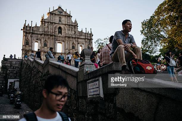 A man rests on a staircase in front of the ruins of St Paul's Cathedral in Macau China on Sunday July 22 2016 Macau is scheduled to release gross...