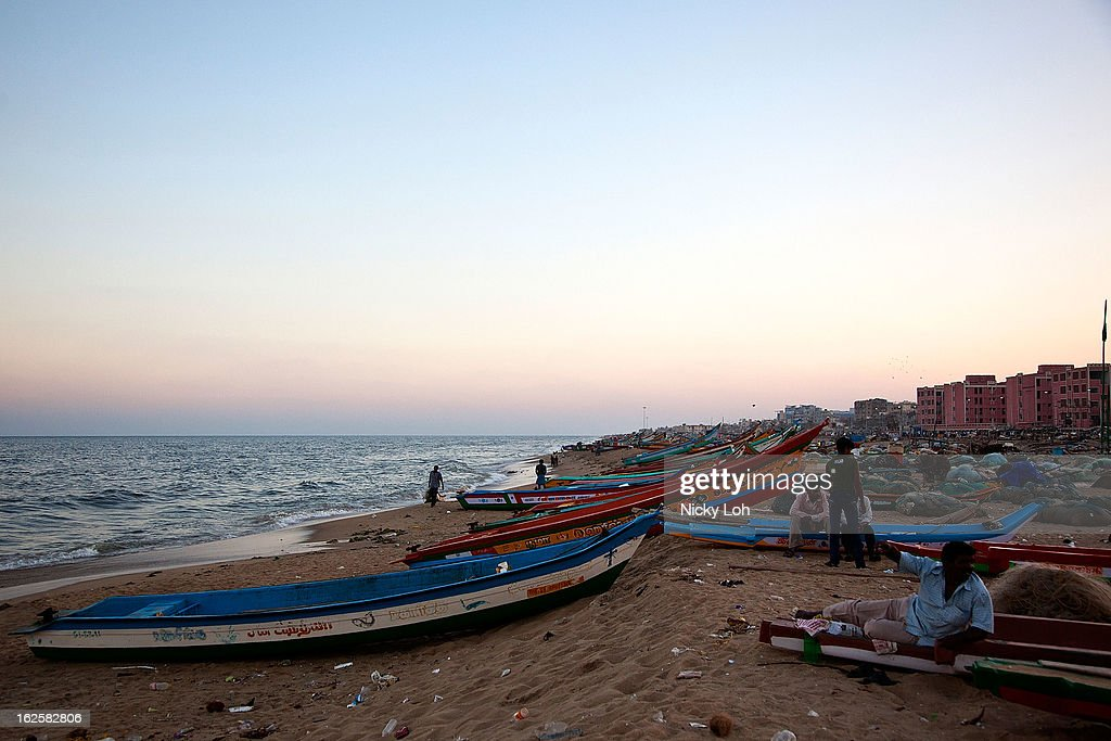 A man rests on his boat during sunset at the Marina Beach on February 24, 2013 in Chennai, India. Marina Beach is an urban beach along the Bay of Bengal, which is part of the Indian Ocean. The beach runs a distance of 13km (8.1 miles), making it the longest natural urban beach in the country and the world's second longest.
