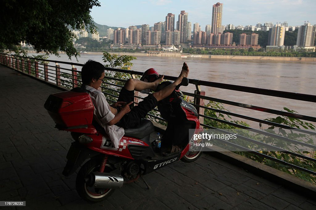 A man rests on his scooter along the bank of the Yangtze River on August 4, 2013 in Chongqing, China. Chongqing is a major city in southwest China and became the municipality was created on 14 March 1997. It known as a 'Mountain City' and 'River City' was constructed on the mountain and along the Yangtze River.