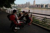 A man rests on his scooter along the bank of the Yangtze River on August 4 2013 in Chongqing China Chongqing is a major city in southwest China and...
