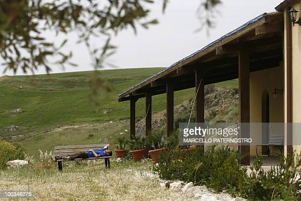 A man rests on May 14 2010 near Corleone on the Italian island of Sicily at the 'Terre di Corleone' a bed and breakfast developped on land...