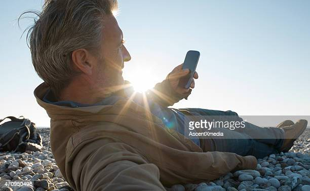 Man rests on pebble beach, send text on smart phone