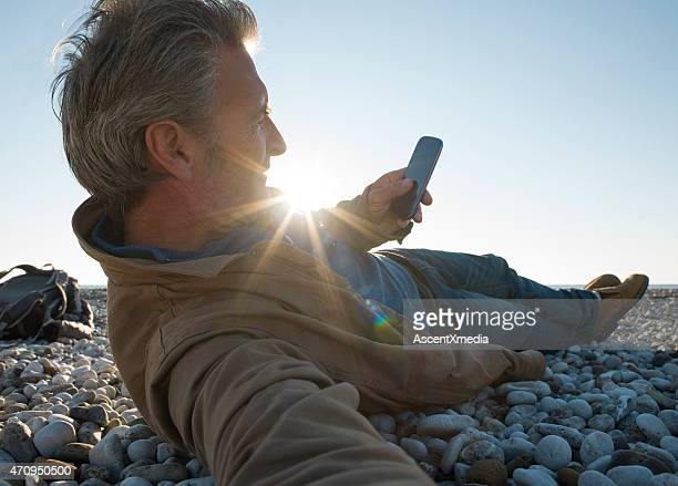 Man rests on pebble beach, sends text on smart phone