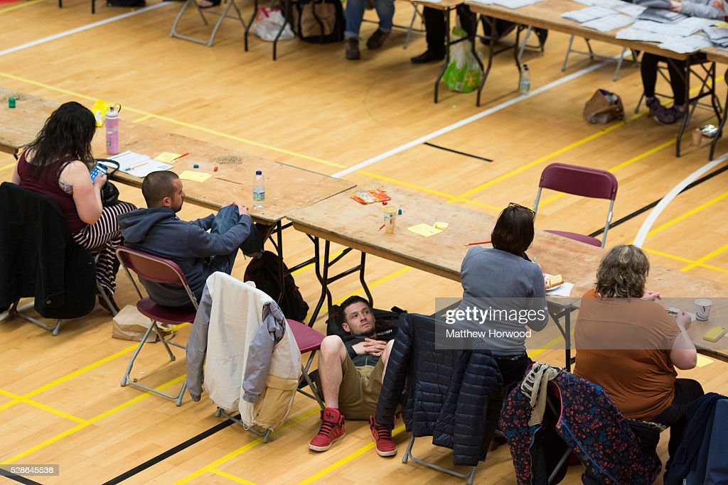 A man rests under a desk as counting runs in to the morning during the National Assembly for Wales election count at the Sport Wales National Centre on May 06, 2016 in Cardiff, Wales. Yesterday the UK went to the polls to vote for assembly members, councillors, mayors and police commissioners.