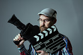 Man Retro movie camera and movie clapper. Bearded thoughtful cinema operator in glasses. The director of documentary and feature films