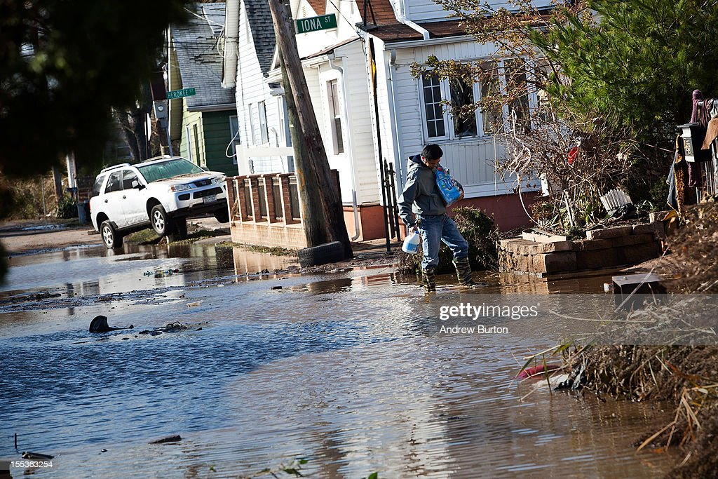 A man returns to his house with bleach and water in the Midland Beach neighborhood of Staten Island on November 3, 2012 in New York City. As clean up efforts from Superstorm Sandy continue, colder weather and another storm predicted for next week are beginning to make some worried.