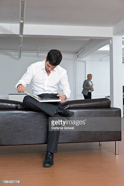 Man reviewing a book on the sofa