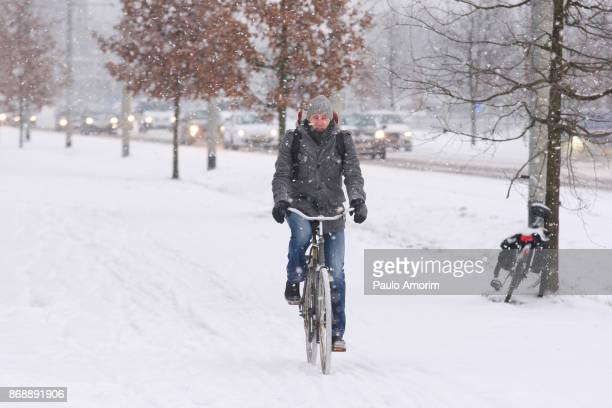 A man ride bicycle on the street covered in snow in Netherlands