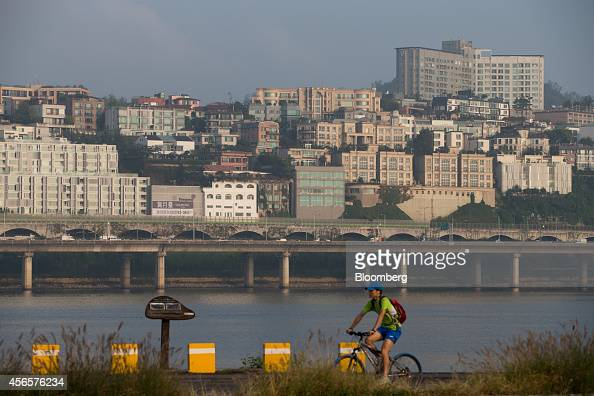 A man rides a bicycle along the Han River past the UN village in Seoul South Korea on Tuesday Sept 30 2014 South Korean President Park Geun Hyes...