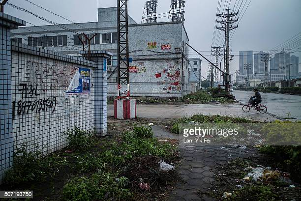 A man rides a bicycle at an abandoned industrial area of Houjie town on January 27 2016 in Dongguan China China's slowing economy and falling stock...