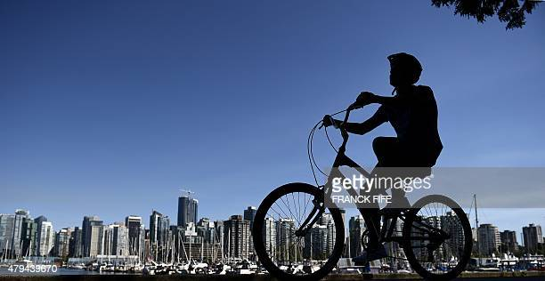 A man rides a bicycle in Stanley Park that borders the downtown area of Vancouver British Columbia on July 3 2015 AFP PHOTO / FRANCK FIFE