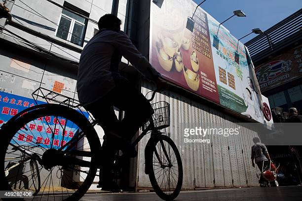 A man rides a bicycle in the Gongbei district of Zhuhai Guangdong province China on Sunday Nov 16 2014 Chinas economy burdened by overcapacity and...