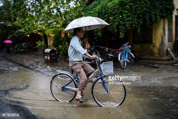 A man rides a bicycle in the town of Hoi An on November 8 2017 following days of heavy rains after Typhoon Damrey hit the coast The death toll from...
