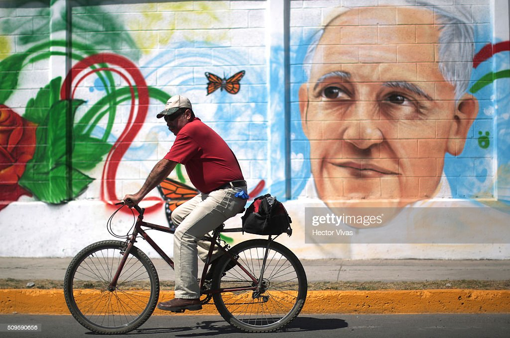 A man rides a bicycle near a graffiti painted to welcome Pope Francis near the esplanade where Pope Francis will give a mass for 300 thousand people during the preparations ahead the visit of Pope Francis to Mexico at Las Americas on February 11, 2016 in Ecatepec, Mexico.
