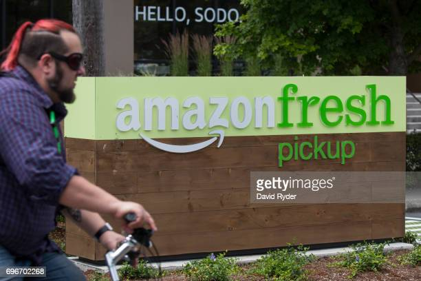 A man rides a bicycle near an AmazonFresh Pickup location on June 16 2017 in Seattle Washington Amazon announced that it will buy Whole Foods Market...