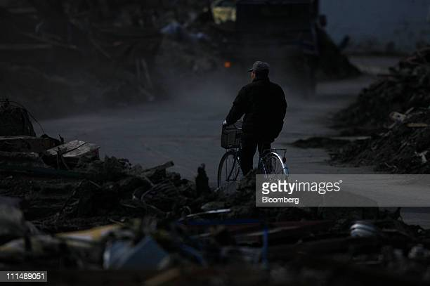 A man rides a bicycle on a road after tsunami debris was removed in Otsuchi town Iwate prefecture Japan on Sunday April 3 2011 Japan begins forging a...