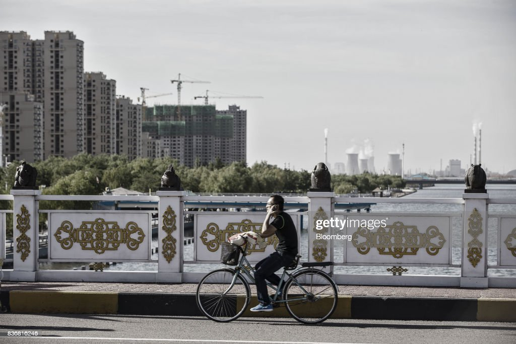 A man rides a bicycle over a bridge as residential buildings and power plants stand in the distance in Baotou, Inner Mongolia, China, on Friday, Aug. 11, 2017. China's economy showed further signs of entering a second-half slowdown, as curbs on property, excess borrowing and industrial overcapacity began to bite. Photographer: Qilai Shen/Bloomberg via Getty Images