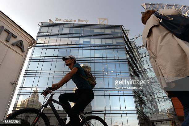 A man rides a bicycle past a building that houses Deutsche Bank's Russian headquarters in Moscow on September 18 2015 Germany's biggest lender...