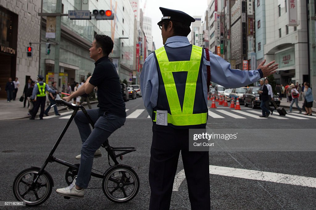A man rides a bicycle past a security guard on May 02, 2016 in the Ginza area of Tokyo, Japan. The Greater Tokyo Area is the most populous metropolitan area in the world with a population of 13,506,607 and is currently ranked first in the world in the Safe Cities Index.