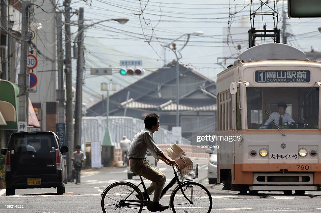 A man rides a bicycle past a tram in Okayama, Japan, on Tuesday, May 21, 2013. The Bank of Japan, forecast to maintain plans for expanded monetary easing at a meeting ending on May 22, is targeting 2 percent inflation in two years after more than 10 years of entrenched deflation. Photographer: Tomohiro Ohsumi/Bloomberg via Getty Images