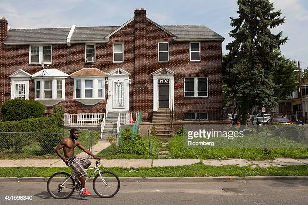 A man rides a bicycle past an abandoned home right with plywood panels painted by artist Chris Toepfer and local residents in Camden New Jersey US on...