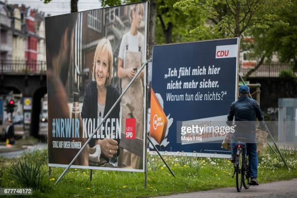 A man rides a bicycle past election campaign billboards of the German Social Democrats and the German Christian Democrats ahead of state elections in...