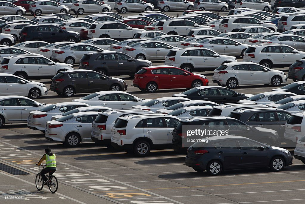 A man rides a bicycle past Kia Motors Corp. vehicles bound for export at the port of Pyeongtaek in Pyeongtaek, South Korea, on Monday, Sept. 30, 2013. South Koreas consumer confidence sank to a five-month low in September, even after a rebound in exports fueled the fastest economic growth in two years last quarter. Photographer: SeongJoon Cho/Bloomberg via Getty Images