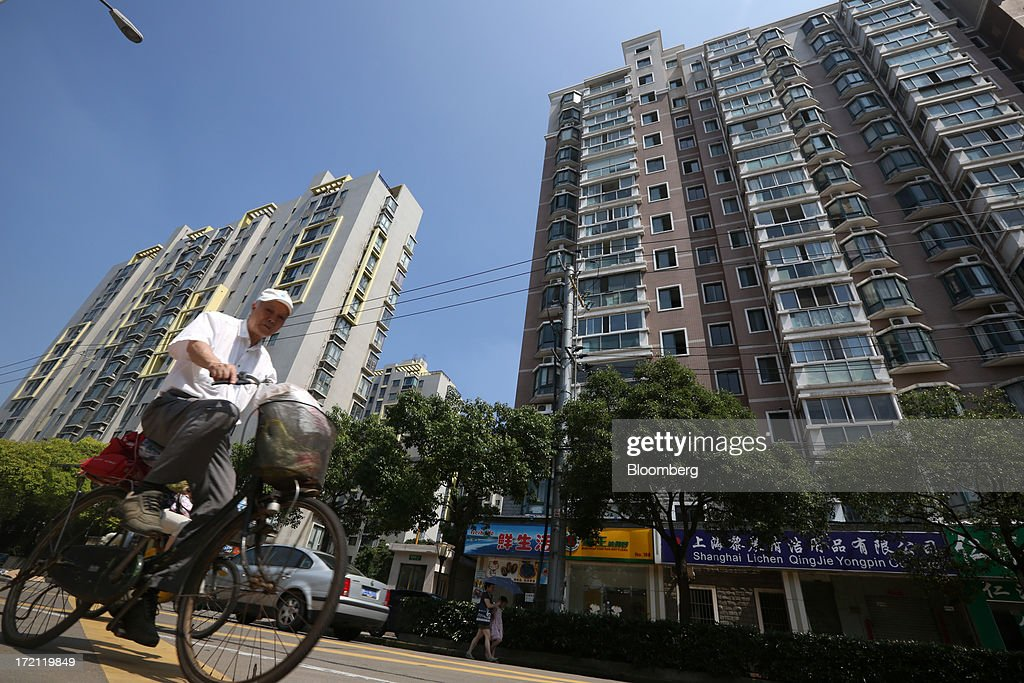 A man rides a bicycle past residential buildings in Shanghai, China, on Sunday, June 30, 2013. China's President Xi Jinping said officials shouldn't be judged solely on their record in boosting gross domestic product, the latest signal that policy makers are prepared to tolerate slower economic expansion. Photographer: Tomohiro Ohsumi/Bloomberg via Getty Images