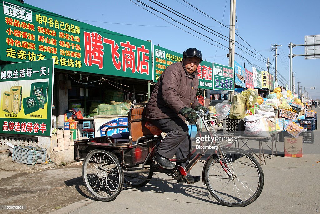 A man rides a bicycle past stores in Pinggu, on the outskirts of Beijing, China, on Saturday, Nov. 17, 2012. China's gross domestic product slowed to 7.4 percent in the July-September period from a year earlier, the weakest in three years. Photographer: Tomohiro Ohsumi/Bloomberg via Getty Images