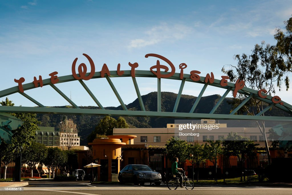A man rides a bicycle past the entrance to The Walt Disney Company studios in Burbank, California, U.S., on Thursday, March 14, 2013. Walt Disney Co. pushed back the release of its Infinity video-game system by two months, postponing a potential source of profit at its interactive unit. Photographer: Patrick T. Fallon/Bloomberg via Getty Images