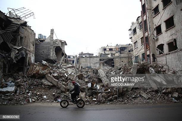A man rides a bicycle past the rubble of a destroyed building in the rebelheld town of Douma on the eastern edges of the Syrian capital Damascus on...