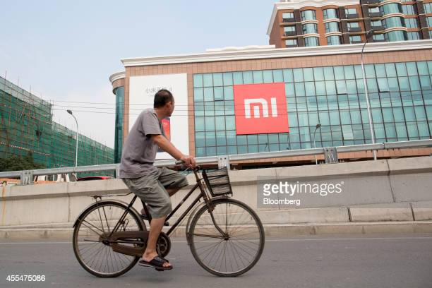 A man rides a bicycle past the Xiaomi Corp logo displayed outside the company's offices in Beijing China on Friday Sept 12 2014 Xiaomi Chief...
