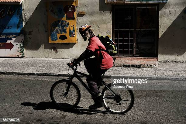 A man rides a bike down a street on December 10 2017 in St John's Antiqua While it's sister island Barbuda was nearly destroyed in Hurricane Irma...