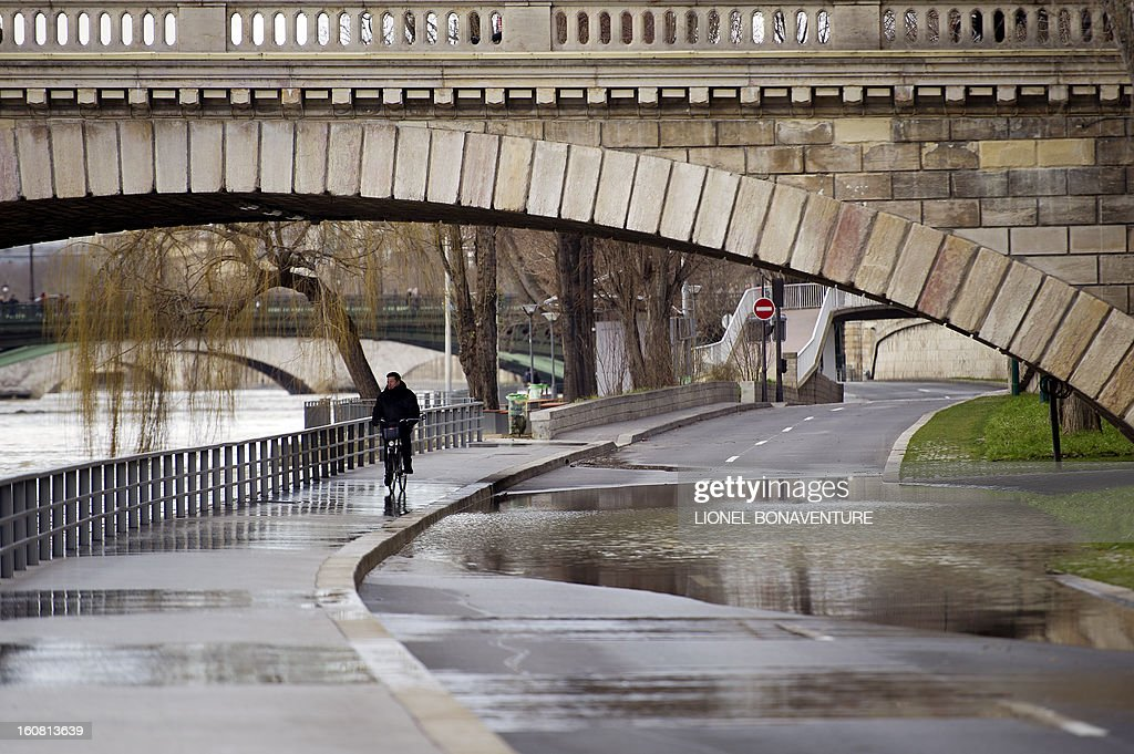 A man rides a bike on an overflowing bank of the Seine river, on February 6, 2013 in Paris. Roads along the river banks were closed to traffic in case of flooding.
