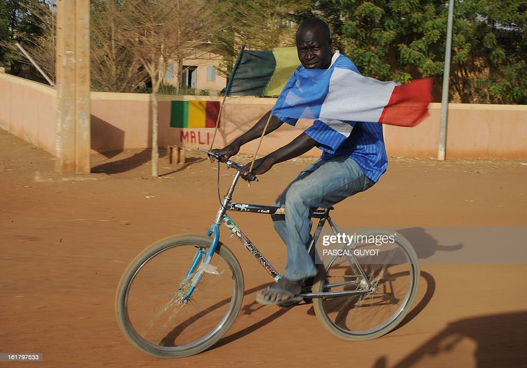 A man rides a bike onto which the handlebars are fixed a Malian and French flag, on February 16, 2013 in central Gao, northern Mali. The European Union yesterday announced fresh aid worth 20 million euros to help restore law and order in Mali as well as the return of basic state services such as education after months of trouble.