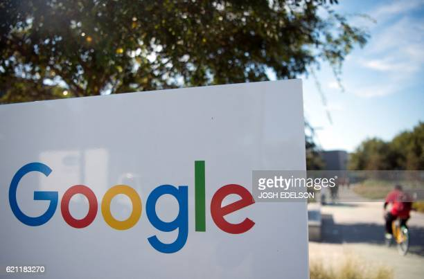 A man rides a bike passed a Google sign and logo at the Googleplex in Menlo Park California on November 4 2016 / AFP PHOTO / JOSH EDELSON