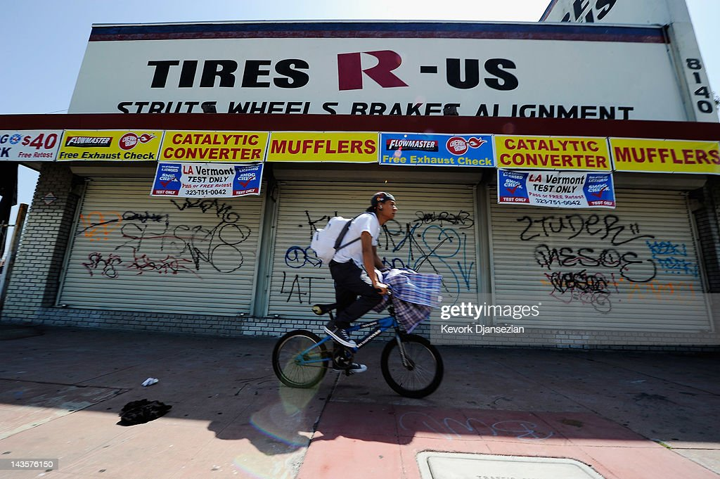 A man rides a bike past a store front full of graffiti in South Los Angeles on April 29, 2012 in Los Angeles, California. It's been 20 years since the verdict was handed down in the Rodney King case that sparked the infamous Los Angeles riots.