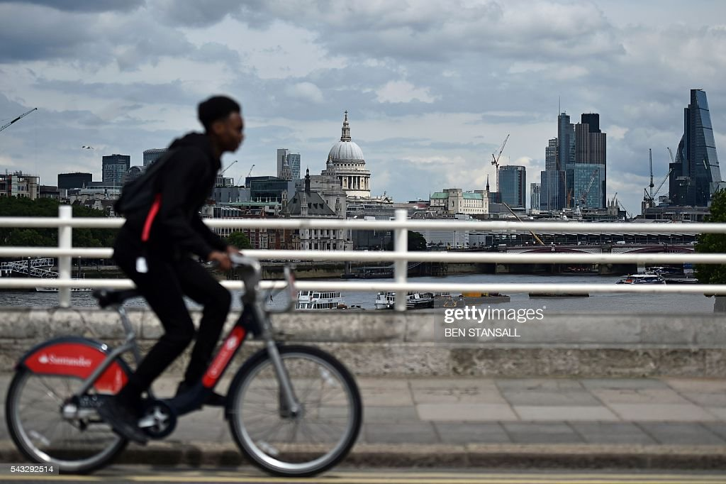 A man rides a 'Boris Bike' over Waterloo bridge with a backdrop of St Paul's Cathedral and buildings in City of London in central London on June 27, 2016. Britain began preparations to leave the European Union on Monday but said it would not be rushed into a quick exit, as markets plunged in the wake of a seismic referendum despite attempts to calm jitters. / AFP / BEN