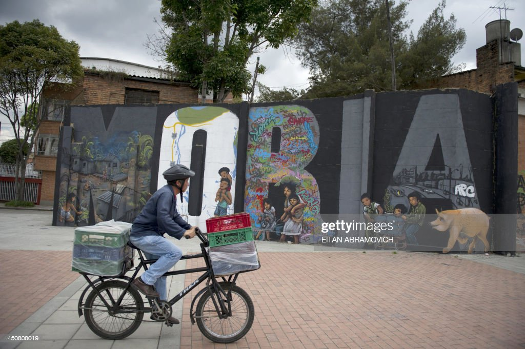 A man rides a bycicle by a graffiti in Bogota on November 19, 2013. The graffiti, once considered vandalism, is gaining more space in Bogota, with a city tour and the support of the mayor's office which provides walls, materials and fees to street artists. AFP PHOTO/Eitan Abramovich /