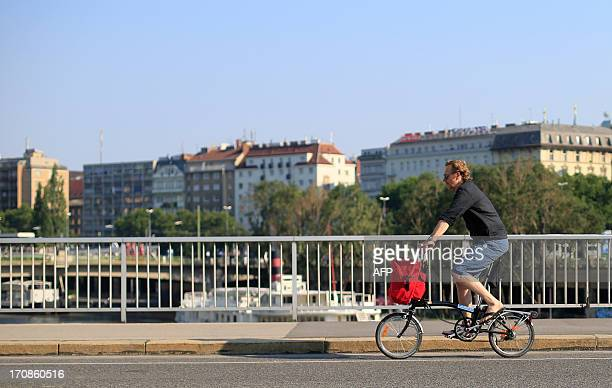 A man rides a foldable bicycle on a sunny and hot day in Vienna on June 19 2013 Temperatures in the Austrian capital reached 35 degrees celsius with...