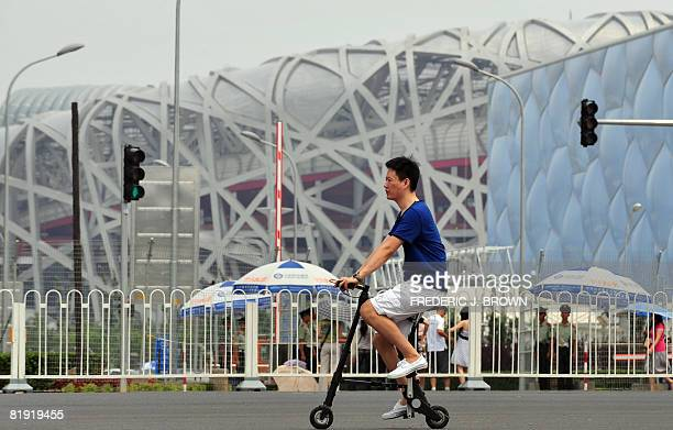 A man rides a foldable bike on tiny wheels on July 13 2008 in Beijing past Olympic venues the National Stadium or Bird's Nest host venue for the...