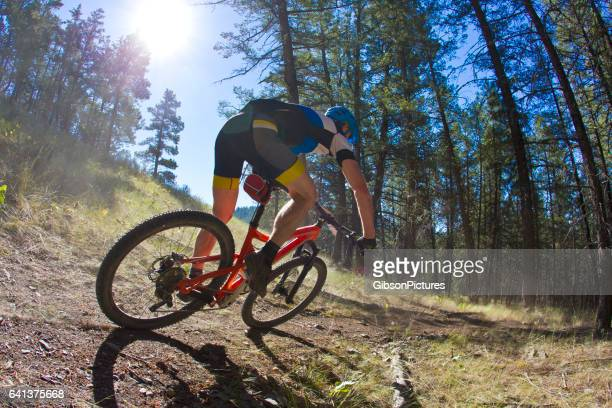 A man rides a high speed corner while competing in a cross-country mountain bike race on a sunny day.