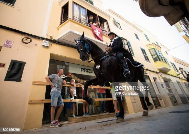 A man rides a horse in the street during the traditional San Juan festival in the town of Ciutadella on the Balearic Island of Menorca on the eve of...
