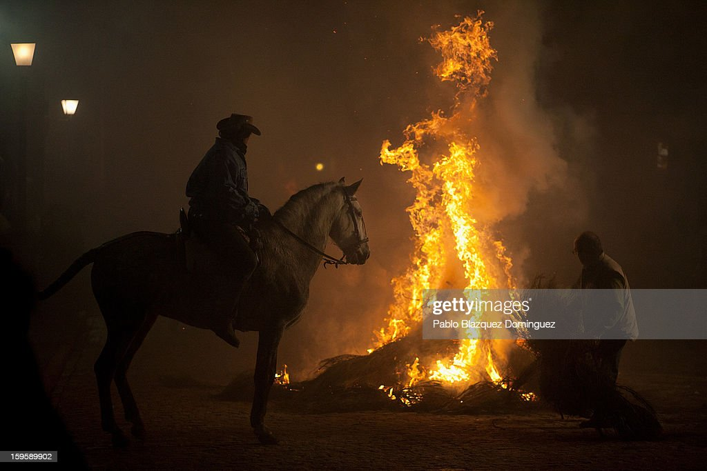A man rides a horse near a bonfire on January 16, 2013 in San Bartolome de Pinares, Spain. In honor of San Anton, the patron saint of animals, horses are riden through the bonfires on the night before the official day of honoring animals in Spain.