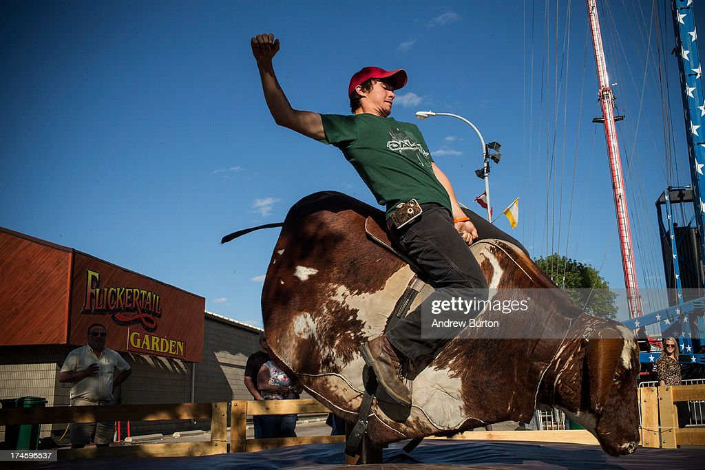 A man rides a mechanical bull at the North Dakota state fair on July 27, 2013 in Williston, North Dakota. The western region of North Dakota has seen a rise in crime, automobile accidents and drug usage recently, due in part to the oil boom which has brought tens of thousands of jobs to the region, lowering state unemployment and bringing a surplus to the state budget.