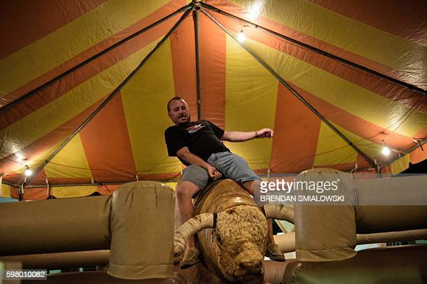 A man rides a mechanical bull during the Shenandoah County Fair August 30 2016 in Woodstock Virginia / AFP / Brendan Smialowski